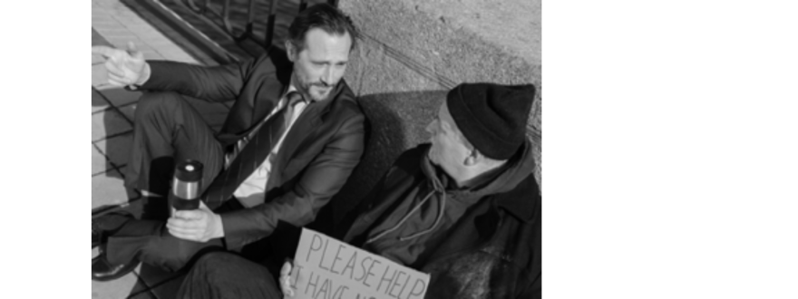 business man in suit and homeless old man sitting together on a sidewalk talking